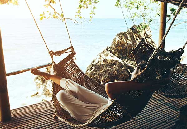 Woman relaxing in hammock by the ocean