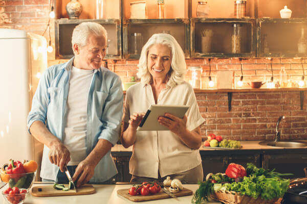 Seniors cooing meal kit in kitchen
