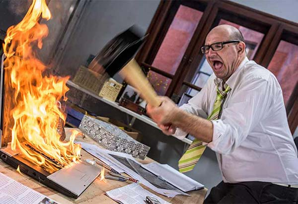 Angry man smashing his on-fire computer
