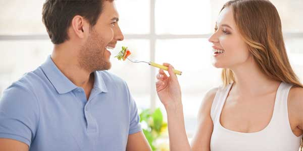 Vegetarian dating couple enjoying salad together