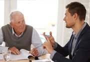 An expert explaining to elderly the top 6 reasons to get a home warranty plan
