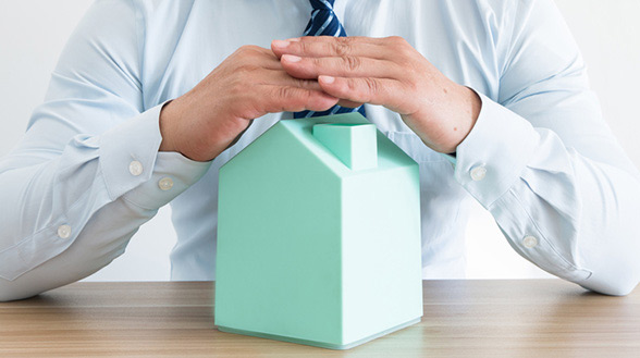 An expert for home warranties cover a small house with his hand to illustrate coverage terms for home warrnties